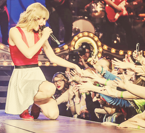 Taylor Swift singing to fans at one of her RED Tour concerts